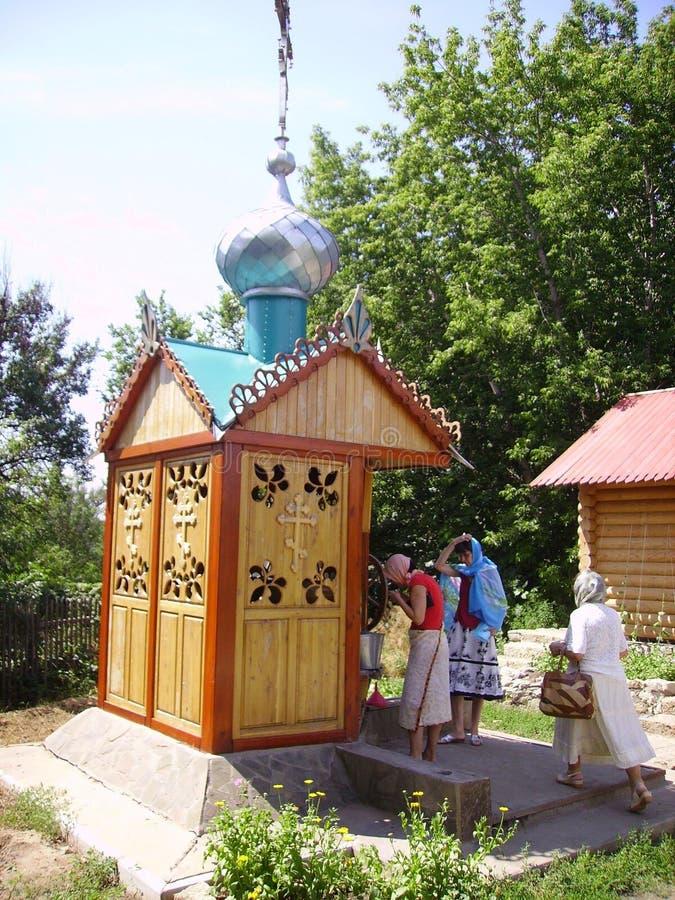 De orthodoxe vrouwenpelgrims verzamelen water in een put met toegewijd water stock afbeelding