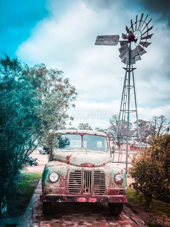 De oude Australische pomp van het binnenland windmil water en uitstekend roestig voertuig royalty-vrije stock foto's