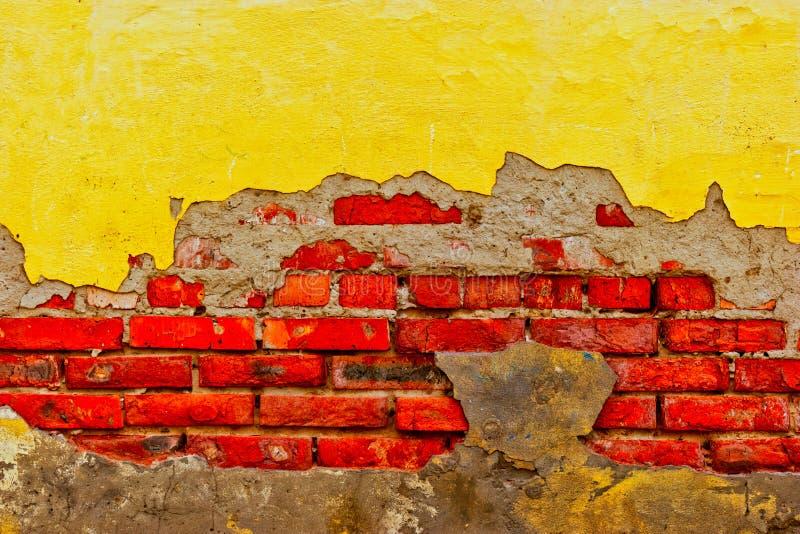 De oude bakstenen muur met de helft destried pleister stock foto's