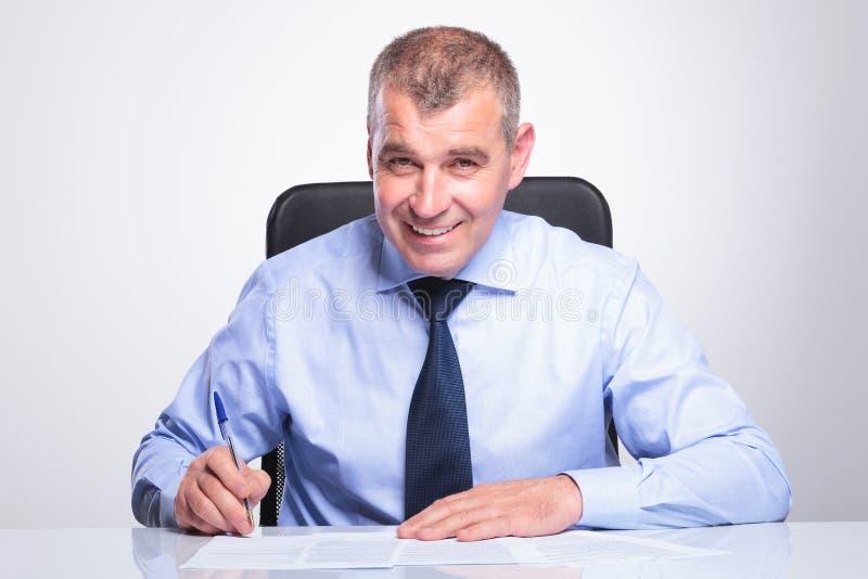 De oude bedrijfsmens ondertekent contracten bij bureau stock foto's