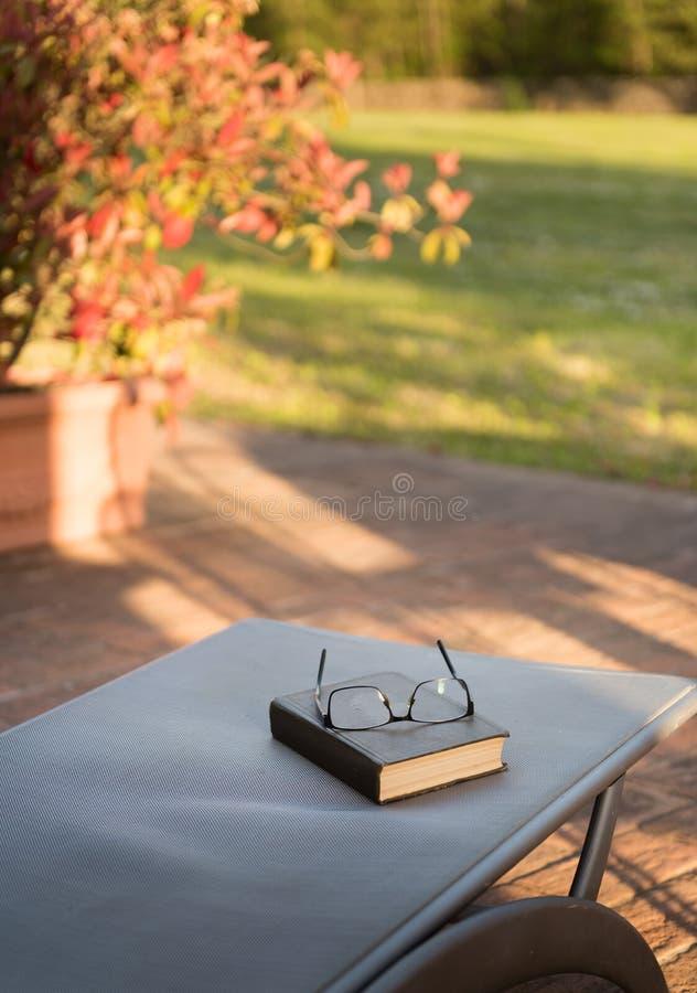 De oude boek en oogglazen voor gelezen en schrijven over vage aard openluchtachtergrond, selectieve nadruk royalty-vrije stock foto's