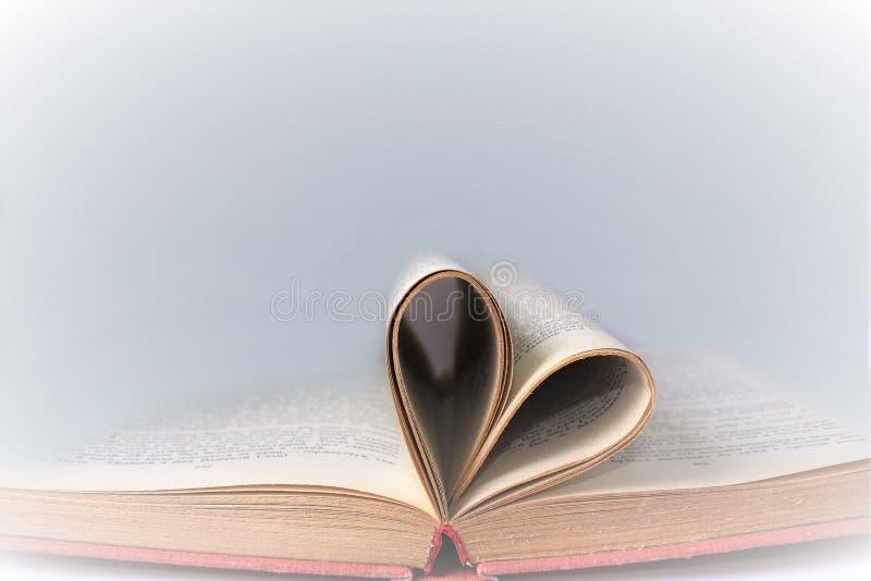De oude boekpagina verfraait aan hartvorm Samenstelling van liefde met open boek dat in hart wordt gerold royalty-vrije stock afbeelding