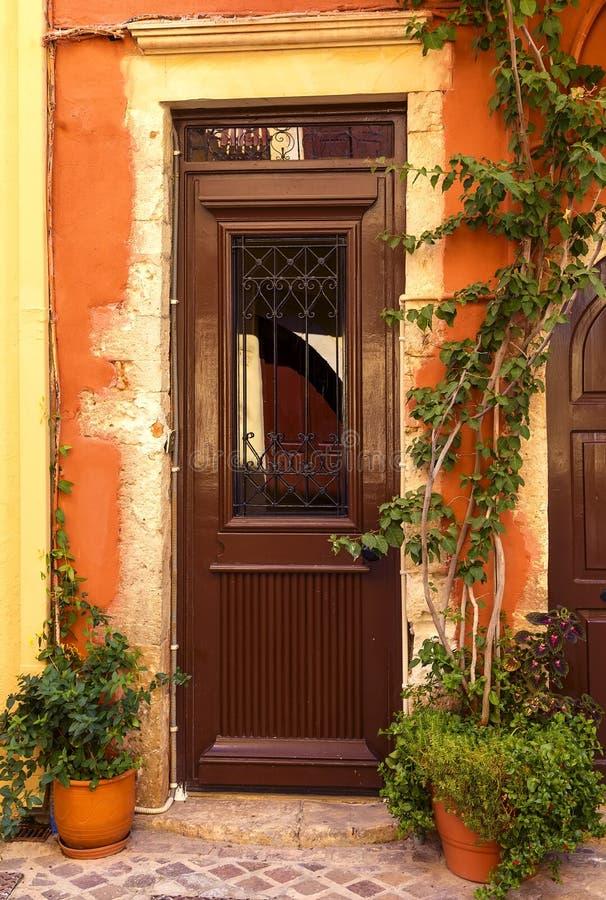 De oude boog houten deur in het gele steenhuis op klein pedestrianized bedekte straat op de zonnige dag stock afbeelding