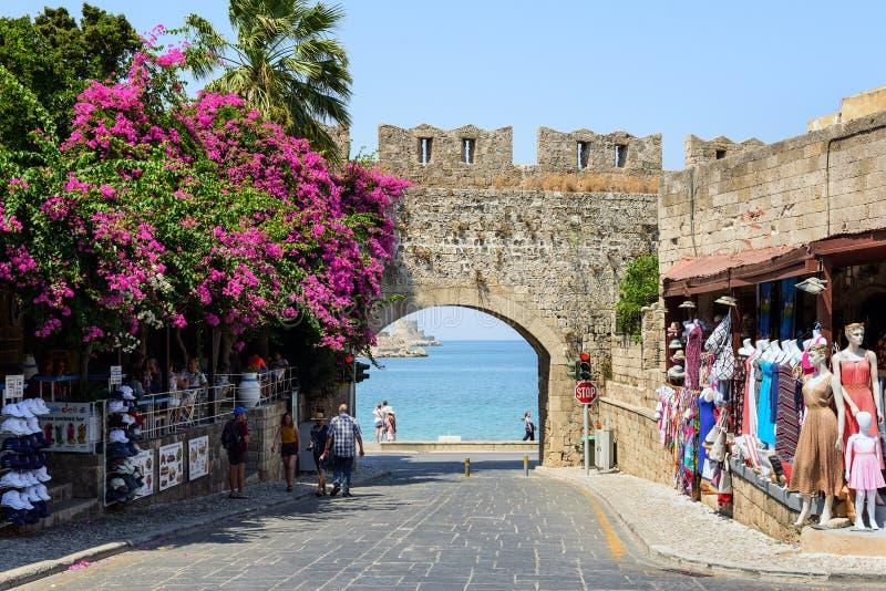 De oude boog in oude muur van de stad van Rhodos met purpere bougainvillea bloeit in de stad van Rhodos op het eiland van Rhodos, stock foto's
