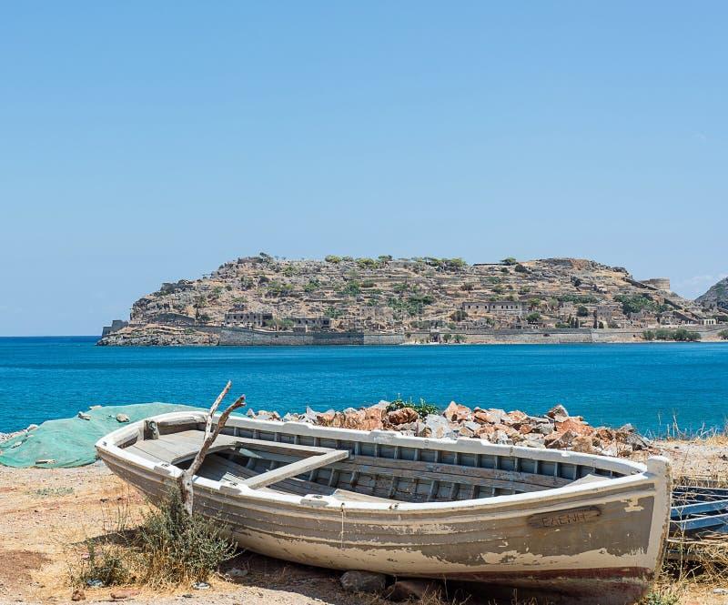 De oude boot ging op de kust met een eiland op de achtergrond verlaten weg royalty-vrije stock foto's