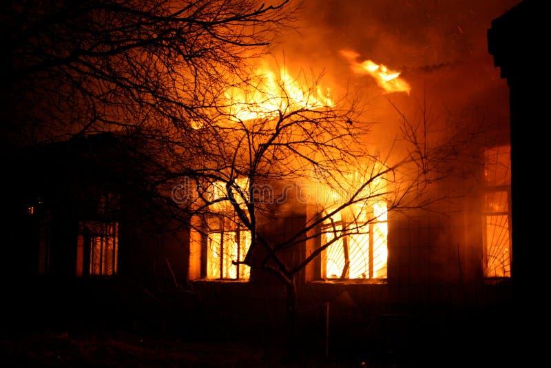 De oude bouw in volledige vlammende vuurhaard stock afbeelding