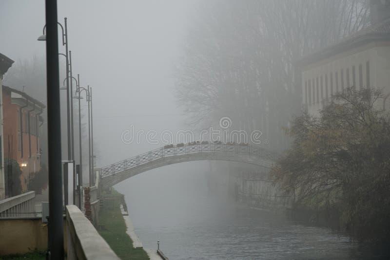 De oude brug van de Boogsteen in mistig weer, de nevelwinter in Italië stock afbeeldingen