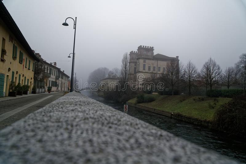 De oude brug van de Boogsteen in mistig weer, de nevelwinter in Italië stock afbeelding