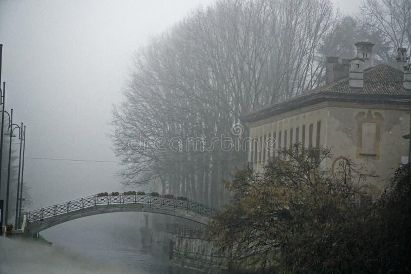 De oude brug van de Boogsteen in mistig weer, de nevelwinter in Italië royalty-vrije stock foto's