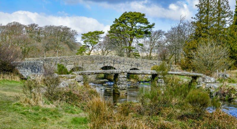 De oude Brug van de de 13de Eeuwsteen op Dartmoor Engeland het UK stock afbeeldingen