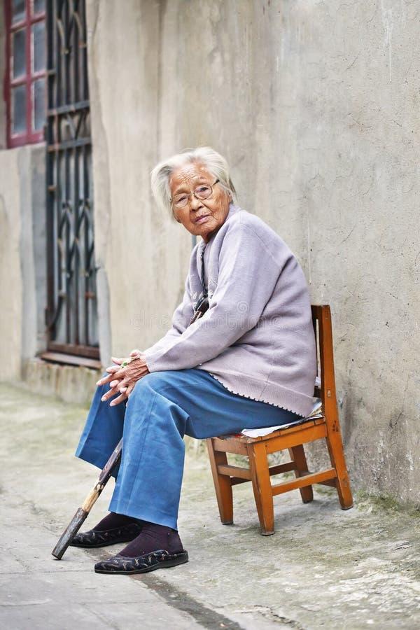 De oude Chinese dame zit buiten op een kleine houten stoel, Yangzhou, China stock fotografie
