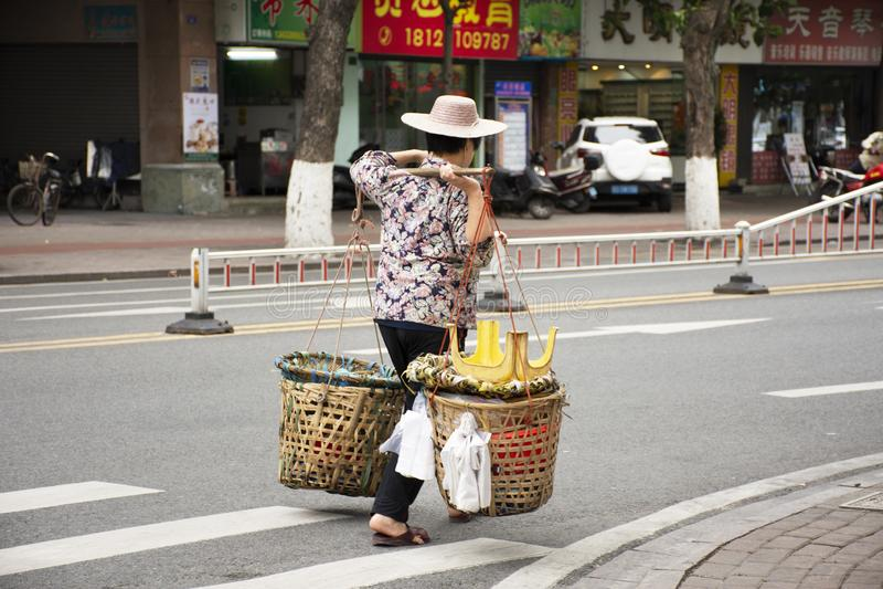 De oude Chinese straatventers die van vrouwenmensen ventermand dragen die naast weg en verkeer in Shantou of Swatow, China lopen stock afbeelding