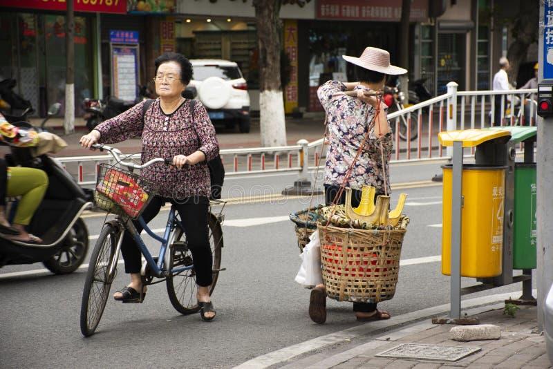 De oude Chinese straatventers die van vrouwenmensen ventermand dragen die naast weg en verkeer in Shantou of Swatow, China lopen royalty-vrije stock afbeeldingen