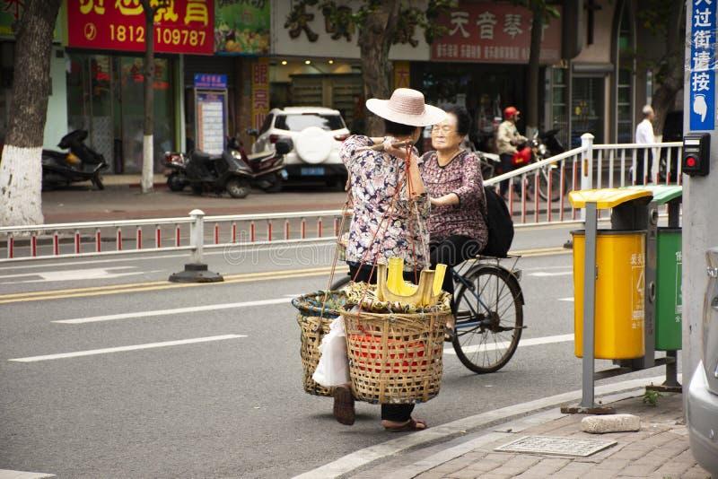 De oude Chinese straatventers die van vrouwenmensen ventermand dragen die naast weg en verkeer in Shantou of Swatow, China lopen royalty-vrije stock fotografie