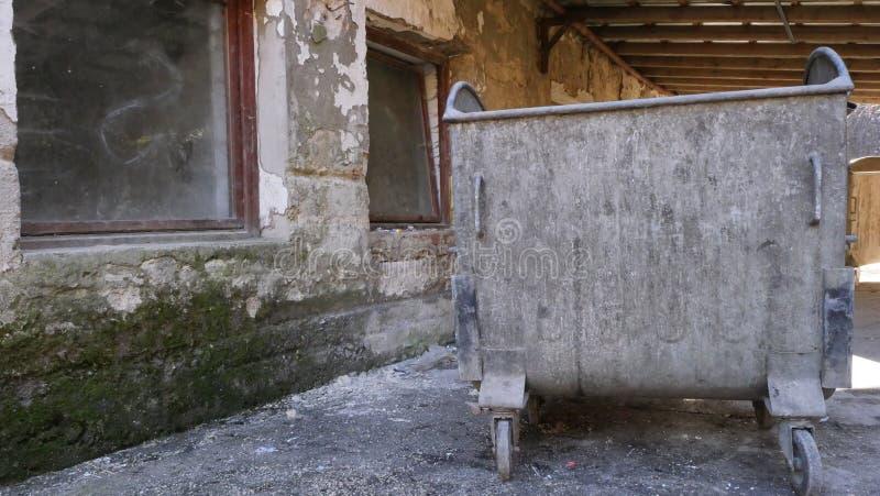De oude container van de metaalbak naast de verlaten bouw met kartonshuisvuil stock afbeeldingen