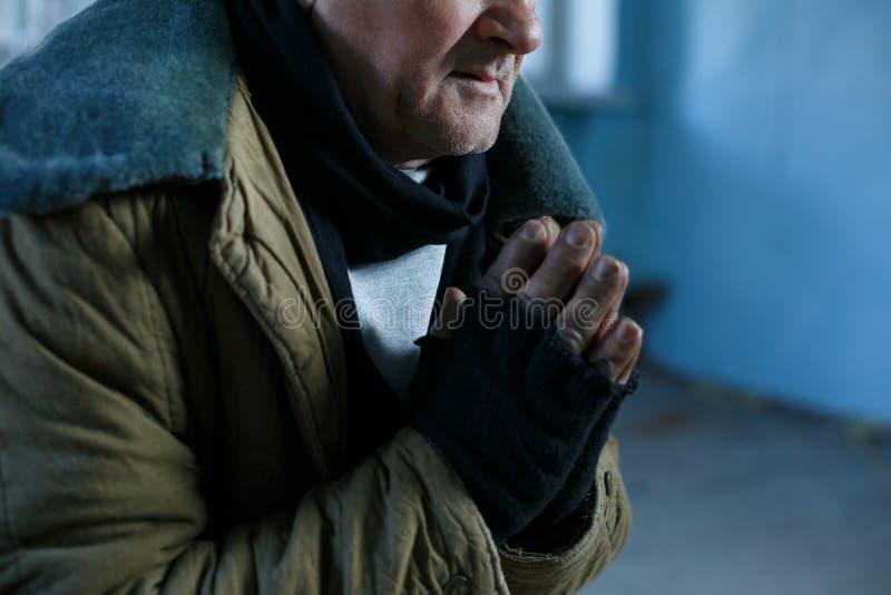 De oude dakloze mens bidt voor hulp royalty-vrije stock foto