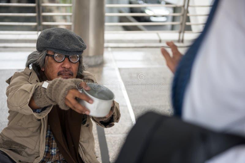 De oude dakloze mens vraagt om geld maar afval stock afbeeldingen