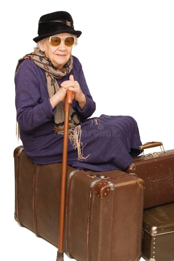 De oude dame zit op een koffer stock fotografie