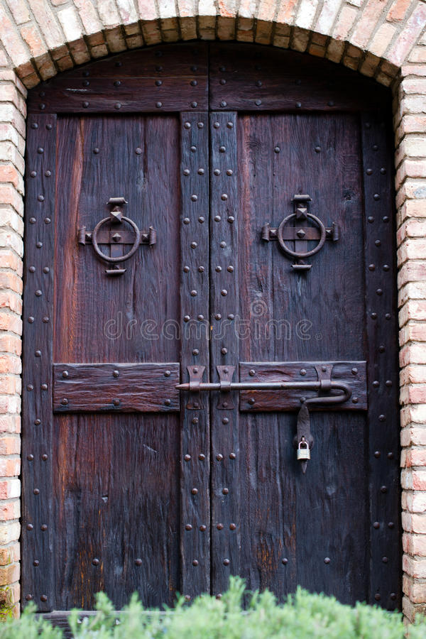 De oude deur smeedde donker natuurlijk hout met klinkslot om hand stock afbeeldingen