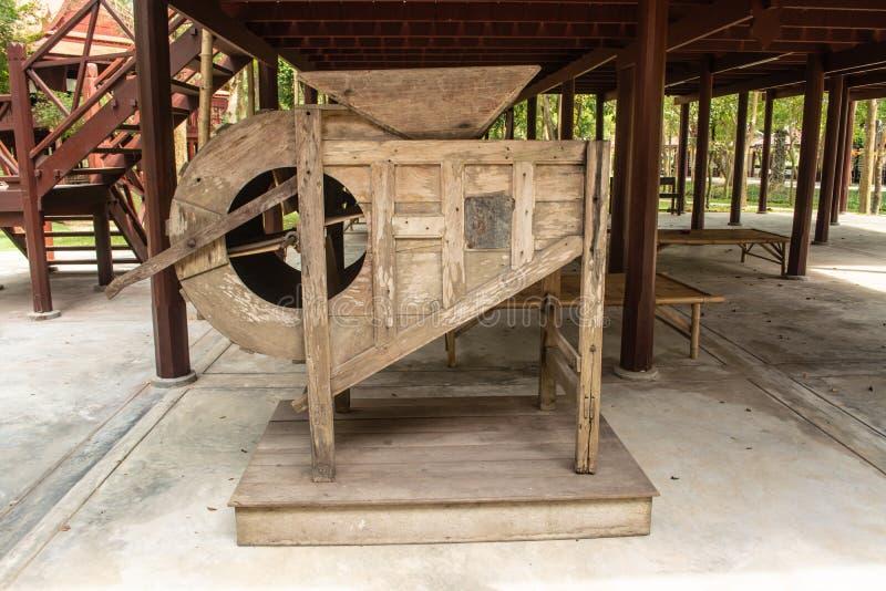De oude die machine van het rijstmalen voor het veranderen van de padie in rijst wordt gebruikt stock afbeeldingen
