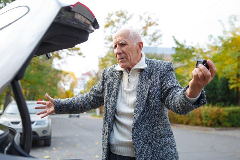 De oude die man dichtbij de boomstam van de auto, met zijn handen wordt teleurgesteld royalty-vrije stock fotografie