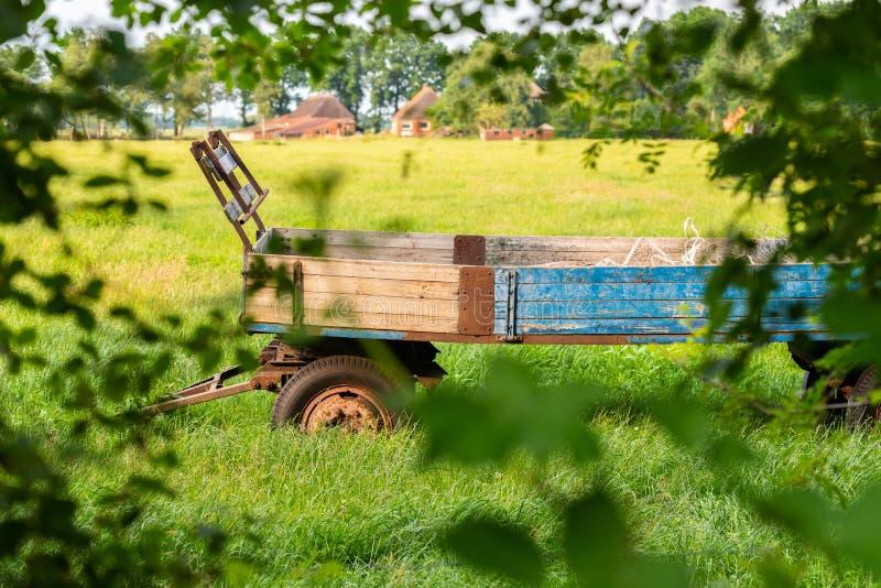 De oude die tribunes van de landbouwbedrijfaanhangwagen op een gebied worden verlaten stock fotografie
