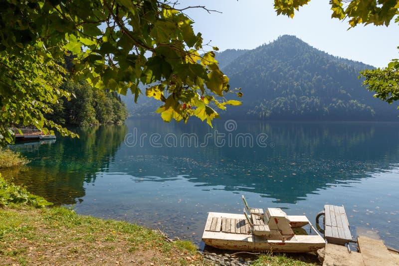 De oude dubbele plaats houten catamaran voor rust blijft dichtbij de kust van het Meer Ritsa, Abchazië, Georgië stock fotografie