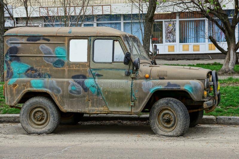 De oude en vuile groene auto bevindt zich aan de kant van de weg op het asfalt stock foto