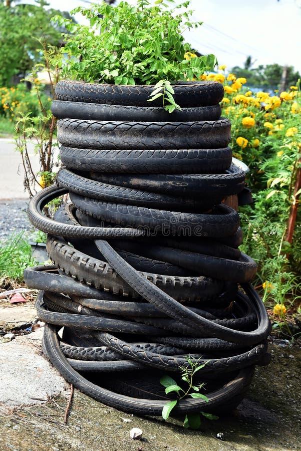 De oude en vuile stapel van motorfietsband op grond na gebruikte oud stock afbeelding