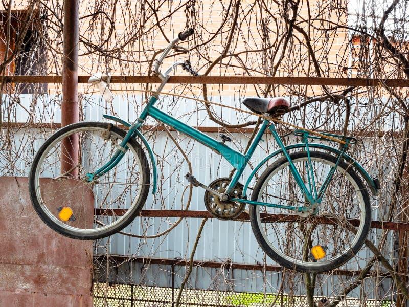 De oude fiets hangt op de omheining van rustieke loods stock foto