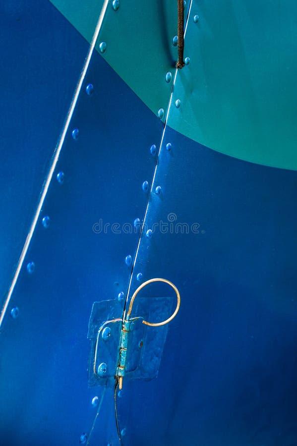 De oude gebogen de scharnierspeld van de metaaldeur op deur en cabine van kleine vliegtuigen schilderde blauw stock foto's
