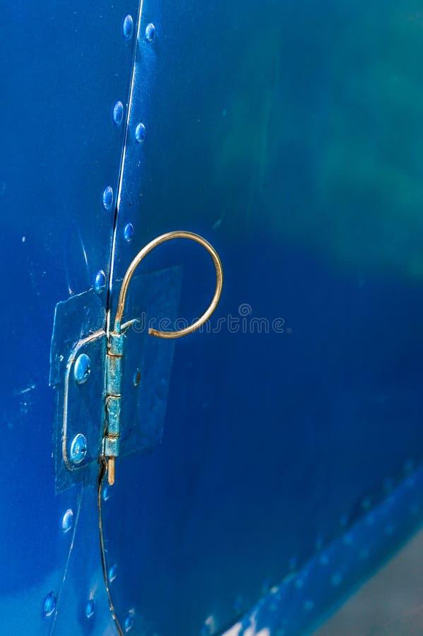 De oude gebogen de scharnierspeld van de metaaldeur op deur en cabine van kleine vliegtuigen schilderde blauw royalty-vrije stock afbeeldingen