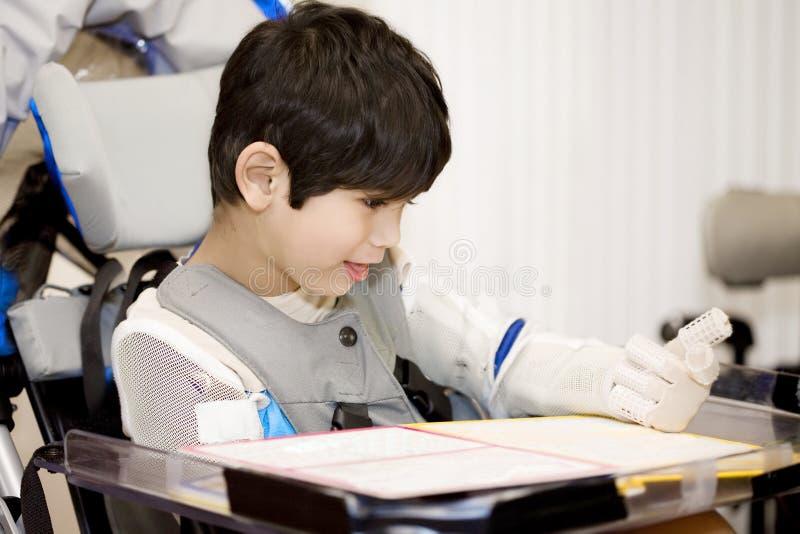 De oude gehandicapte jongen die van vijf jaar in rolstoel bestudeert stock foto