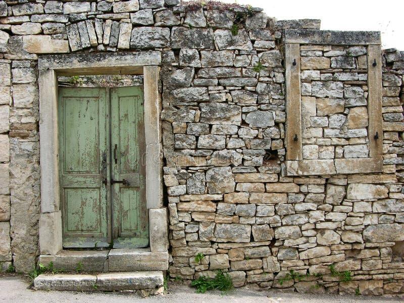 De oude geruïneerde steen maakte muur met groene deur en raamkozijn in Zminj in Istria, Kroatië stock foto's