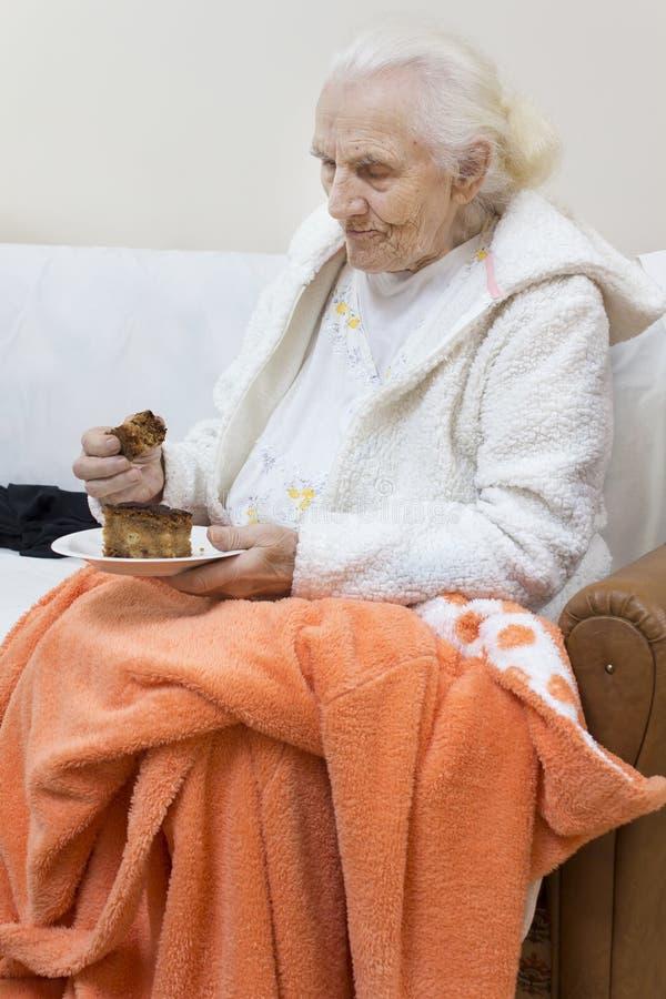 De oude grijs-haired vrouw in een witte peignoir zit op een bank en eet een cake van een schotel royalty-vrije stock afbeeldingen