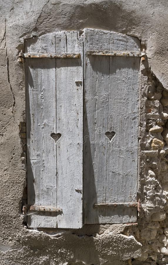 De oude grijze blinden met hart gaven gaten in oude muur van de middeleeuwse bouw in stad van riez in de Franse Provence gestalte stock foto's