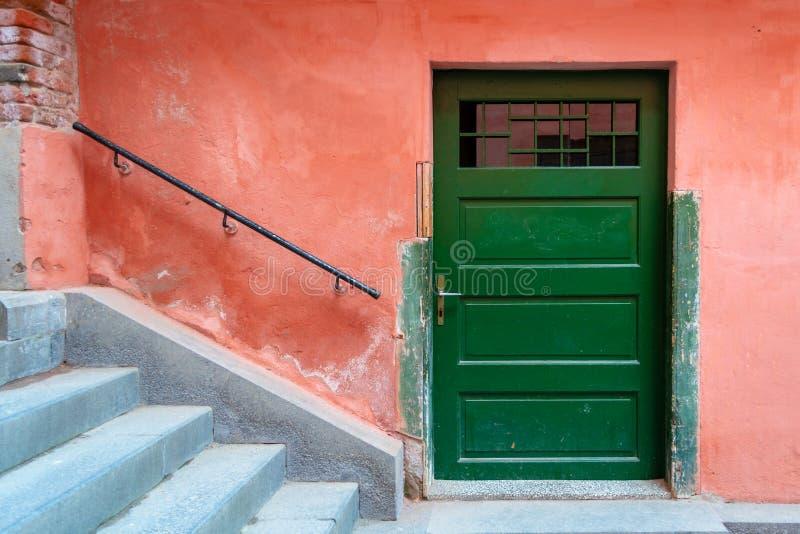 De oude groene houten deur, rode verschrompelde muur, treden met traliewerk, richtte zich volkomen om een abstracte stadsscène te stock foto