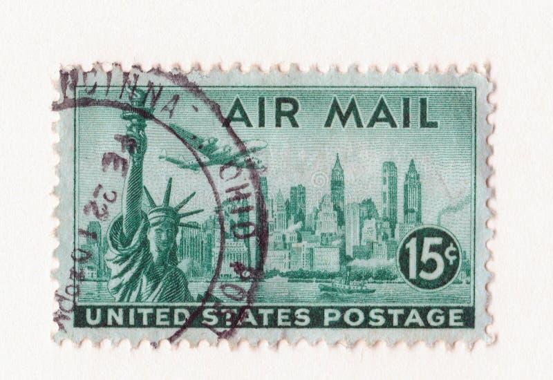 De oude groene uitstekende Amerikaanse postzegel van de luchtpost met het standbeeld van vrijheid Manhattan en een vliegtuig royalty-vrije stock fotografie