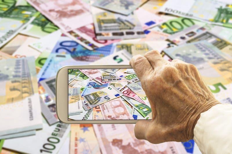 De Oude Hand Neemt Een Beeld Van Euro Bankbiljetten Op Slimme Telefoon Stock Foto