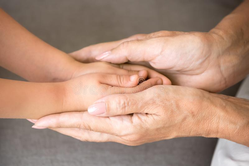 De oude handen van de grootmoederholding van weinig kleindochter, sluiten omhoog stock foto's