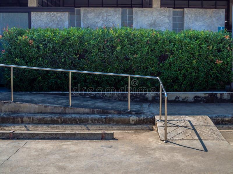 De oude helling van de grungerolstoel met metaalbar dichtbij leeg autoparkeren stock foto's