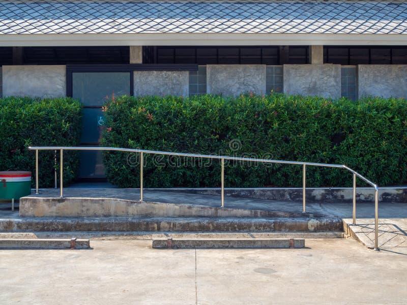 De oude helling van de grungerolstoel met metaalbar dichtbij leeg autoparkeren royalty-vrije stock afbeelding