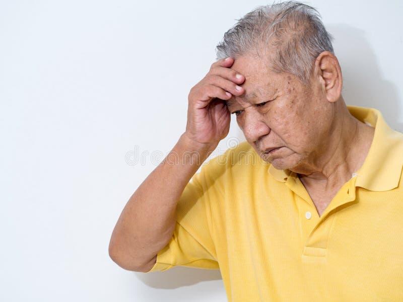De oude hogere mens die en aan gezicht lijden behandelen met dient hoofdpijn en diepe depressie in emotionele wanorde, zorg en wa royalty-vrije stock foto
