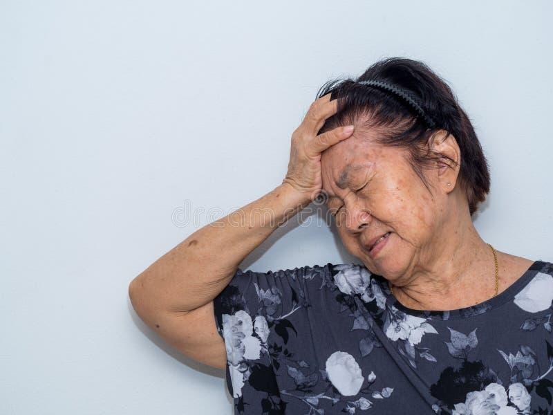 De oude hogere vrouw die en aan gezicht lijden behandelen met dient hoofdpijn en diepe depressie in emotionele wanorde, zorg en w stock foto
