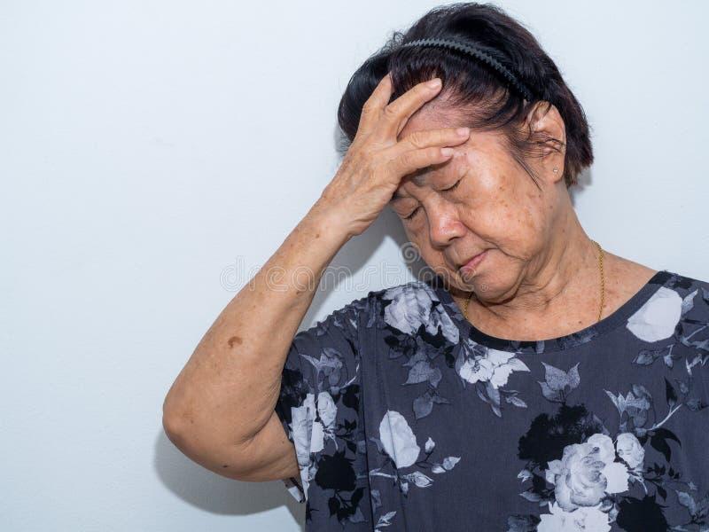 De oude hogere vrouw die en aan gezicht lijden behandelen met dient hoofdpijn en diepe depressie in emotionele wanorde, zorg en w stock fotografie