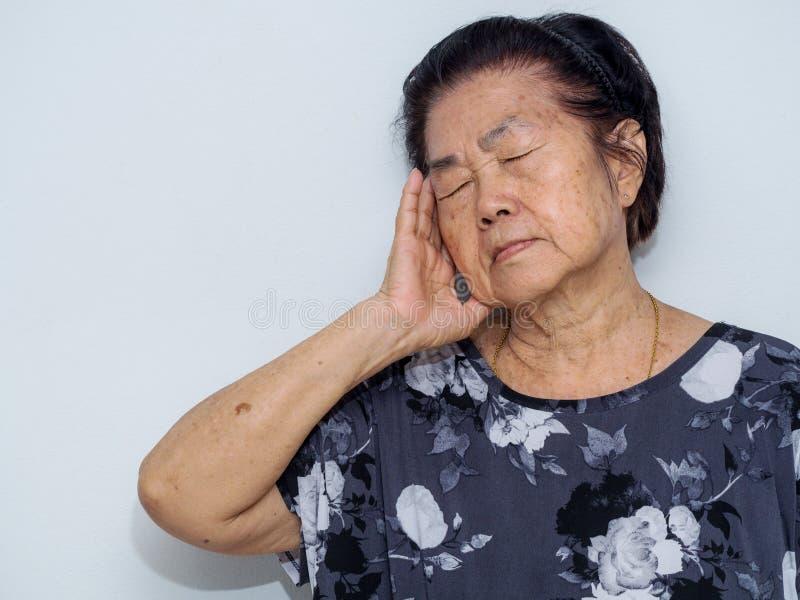 De oude hogere vrouw die en aan gezicht lijden behandelen met dient hoofdpijn en diepe depressie in emotionele wanorde, zorg en w royalty-vrije stock afbeeldingen