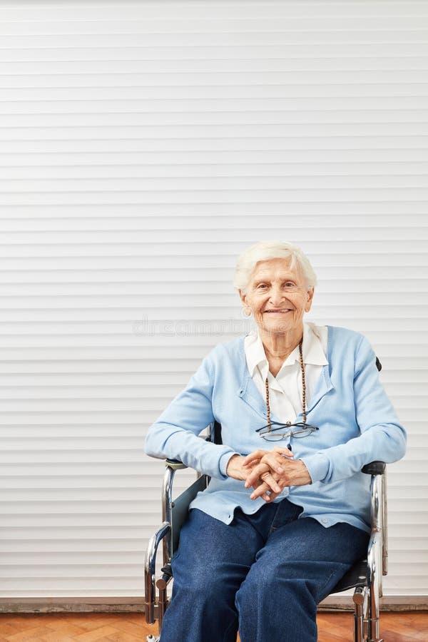 De oude hogere vrouw zit het glimlachen in rolstoel stock fotografie