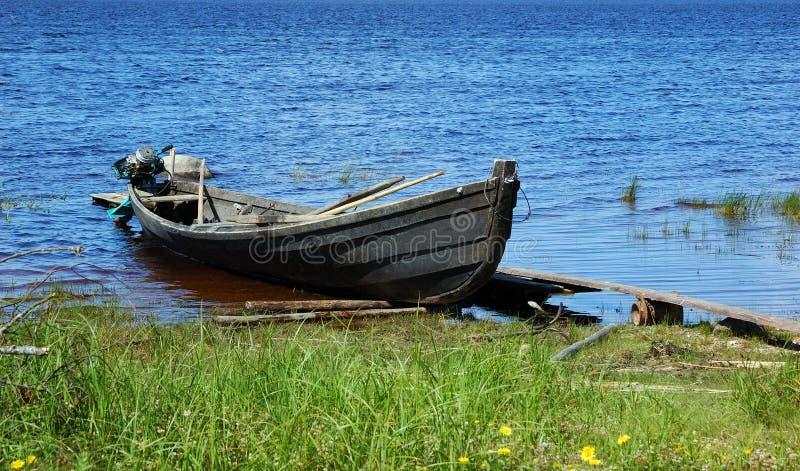 De oude houten boot van de visserijmotor door de meerbank stock afbeeldingen
