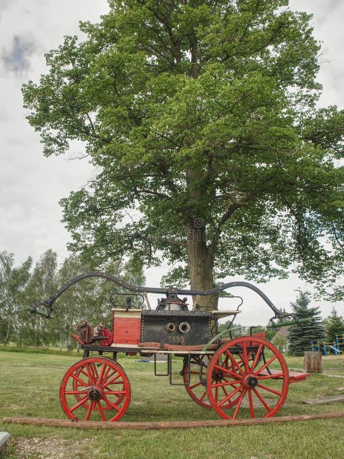 De oude houten brandvrachtwagen op gras Uitstekende houten brandvrachtwagen stock foto's