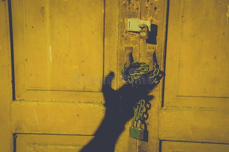 De oude houten die deur met roestige ketting en hangslot en schaduwmensenhand wordt gesloten opent de deur bij nachthuis royalty-vrije stock afbeelding